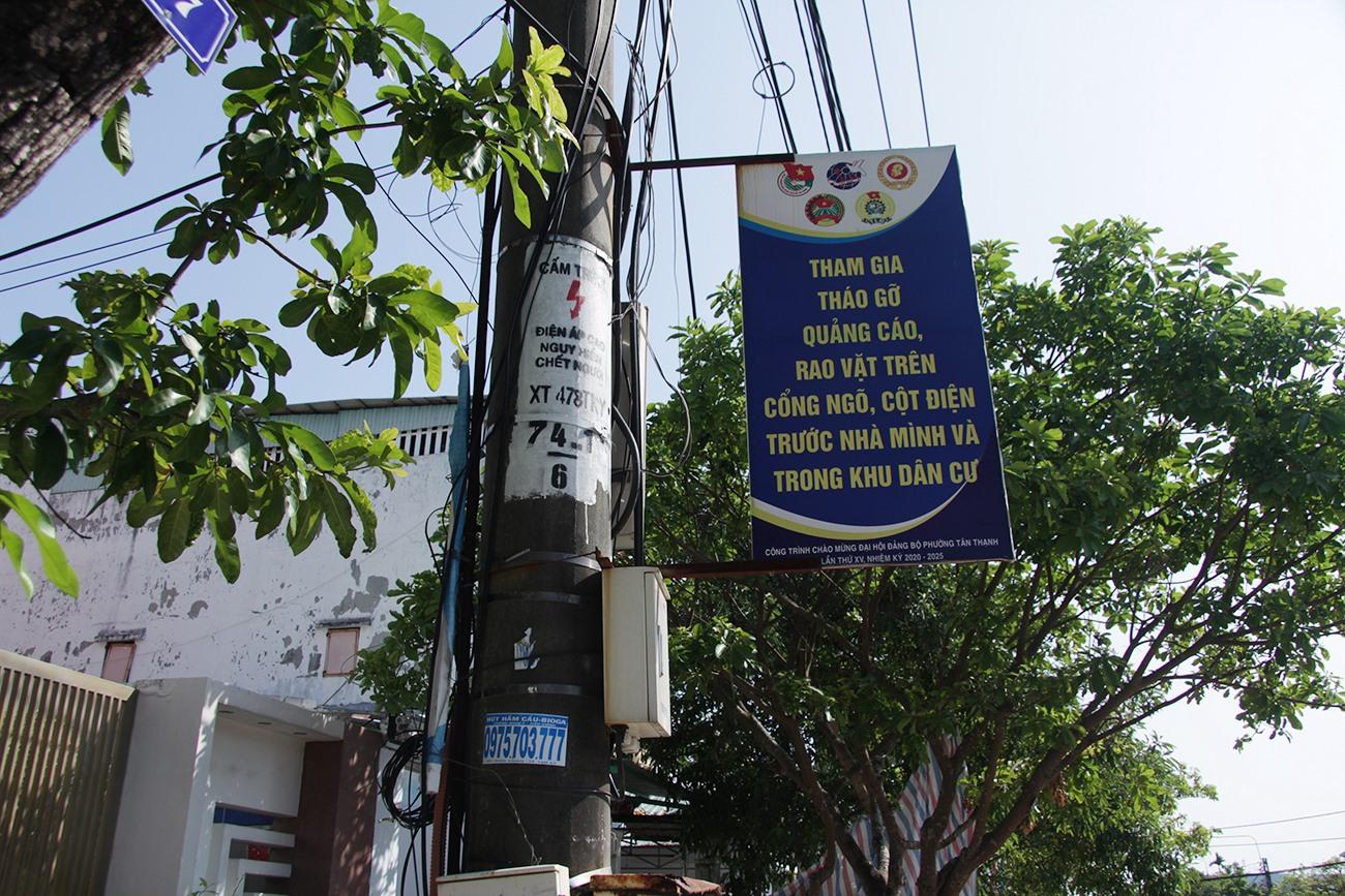 Phướn tuyên truyền người dân tháo gỡ quảng cáo, rao vặt trên cột điện nhưng phía dưới lại bị dán rao vặt.