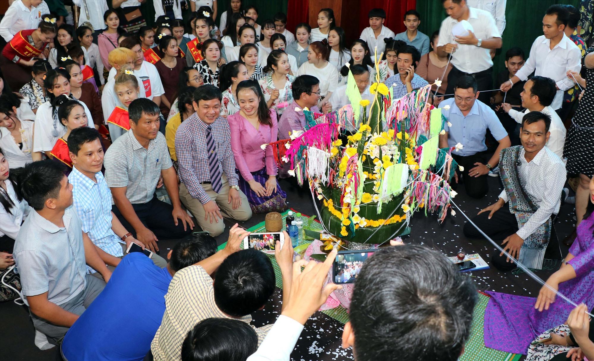 Các đại biểu tham gia nghi lễ mừng năm mới cùng với lưu học sinh Lào. Ảnh: CHÂU HÙNG.