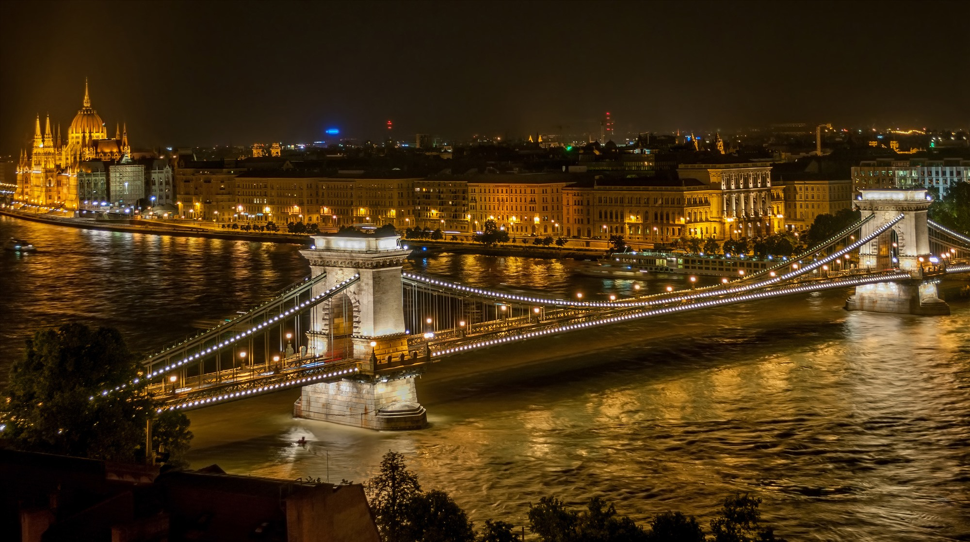 Chain Bridge is in Budapest, Hungary. The bridge makes the city more charming and attractive to visitors, especially at night.