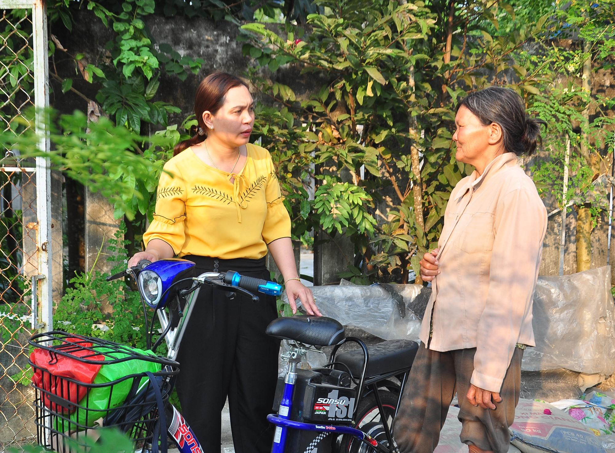 Được Hội LHPN xã phối hợp với Mặt trận mua tặng chiếc xe đạp điện, bà Trương Thị Vân (bên phải) bớt vất vả hơn với nghề bán vé số. Ảnh: VINH ANH