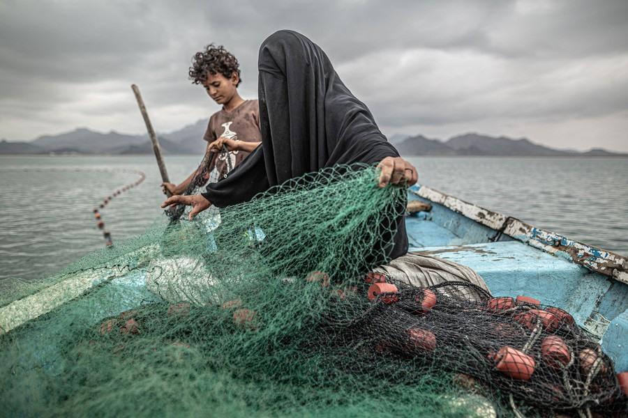Fatima và con trai chuẩn bị lưới đánh cá trên một chiếc thuyền ở vịnh Khor Omeira, Yemen, vào ngày 12 tháng 2. Fatima có chín người con. Để cung cấp cho họ, cô ấy kiếm sống bằng nghề đánh cá. Mặc dù ngôi làng của cô bị tàn phá bởi xung đột vũ trang ở Yemen, Fatima vẫn quay lại tiếp tục sinh kế, mua một chiếc thuyền bằng số tiền kiếm được từ việc bán cá. Xung đột - giữa phiến quân Hồi giáo dòng Shia Houthi và liên minh Ả Rập dòng Sunni do Ả Rập Xê-út dẫn đầu - bắt đầu từ năm 2014 và đã dẫn đến điều mà UNICEF gọi là cuộc khủng hoảng nhân đạo lớn nhất thế giới. Khoảng 20,1 triệu người (gần 2/3 dân số) yêu cầu hỗ trợ lương thực vào đầu năm 2020, với khoảng 80% dân số dựa vào viện trợ nhân đạo. #