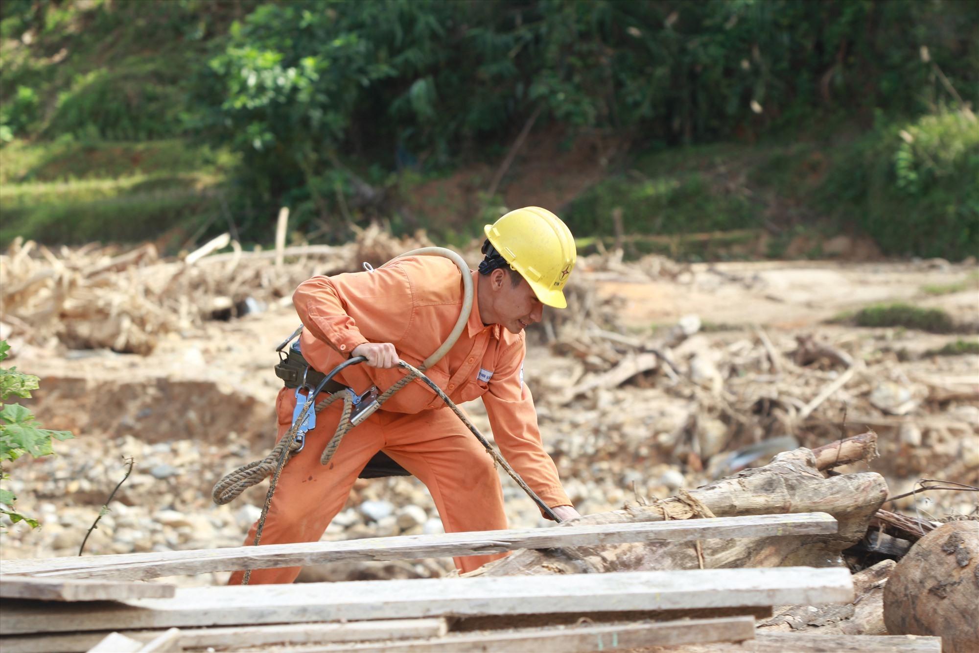 Nhân viên Điện lực Hiệp Đức có mặt tại xã Phước Thành, triển khai khắc phục sự cố ngay sau khi đường sá được thông trở lại mùa bão lũ năm 2020. Ảnh: T.C