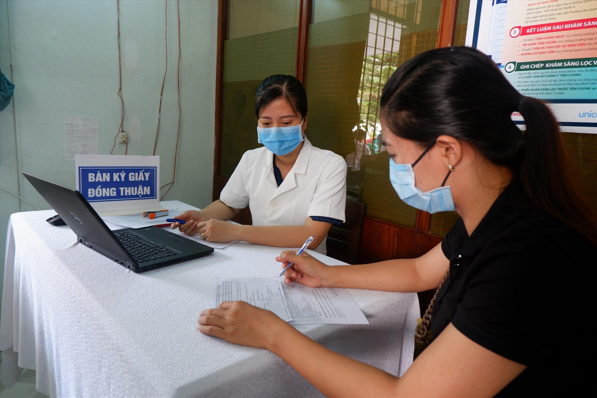Người được tiêm phải ký xác nhận vào phiếu đồng thuận mới được thực hiện tiêm chủng. Ảnh: X.H