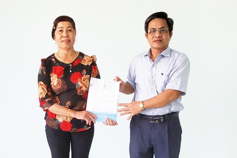 Bà Trần Thị Cúc nhận quyết định hưu trí từ cơ quan BHXH huyện Núi Thành.