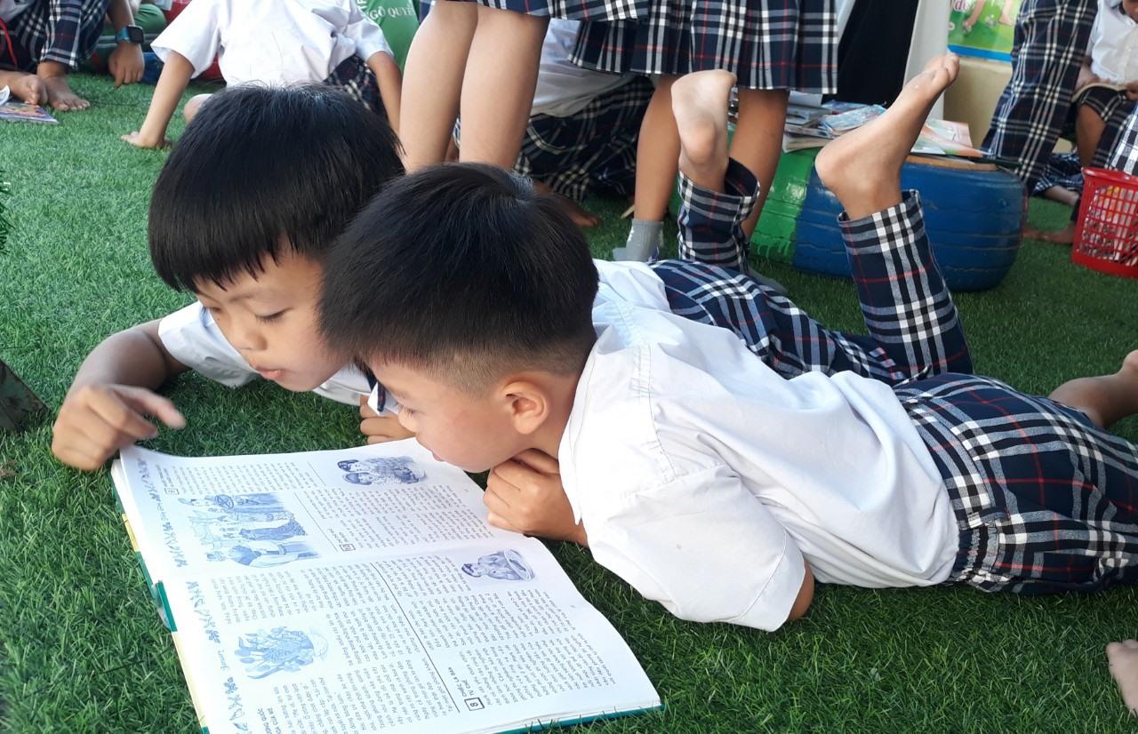 Học sinh Trường Tiểu học Ngô Quyền (Tam Kỳ) đọc sách tại thư viện cộng đồng trong sân trường. Ảnh: C.N
