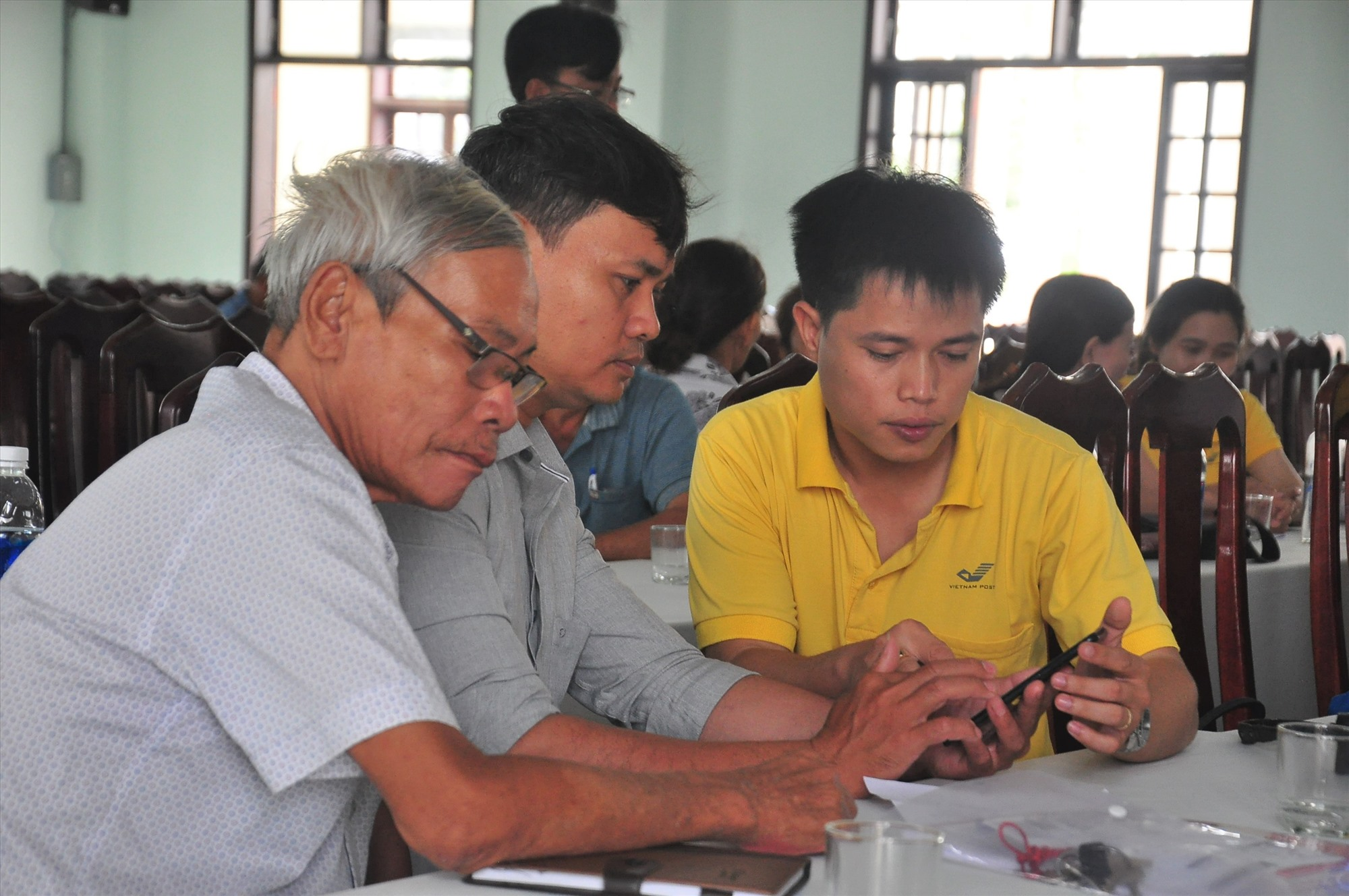 Nhân viên Bưu điện Quảng Nam hỗ trợ người dân cài đặt App công dân số và thực hiện định danh xác thực điện tử. Ảnh: A.H