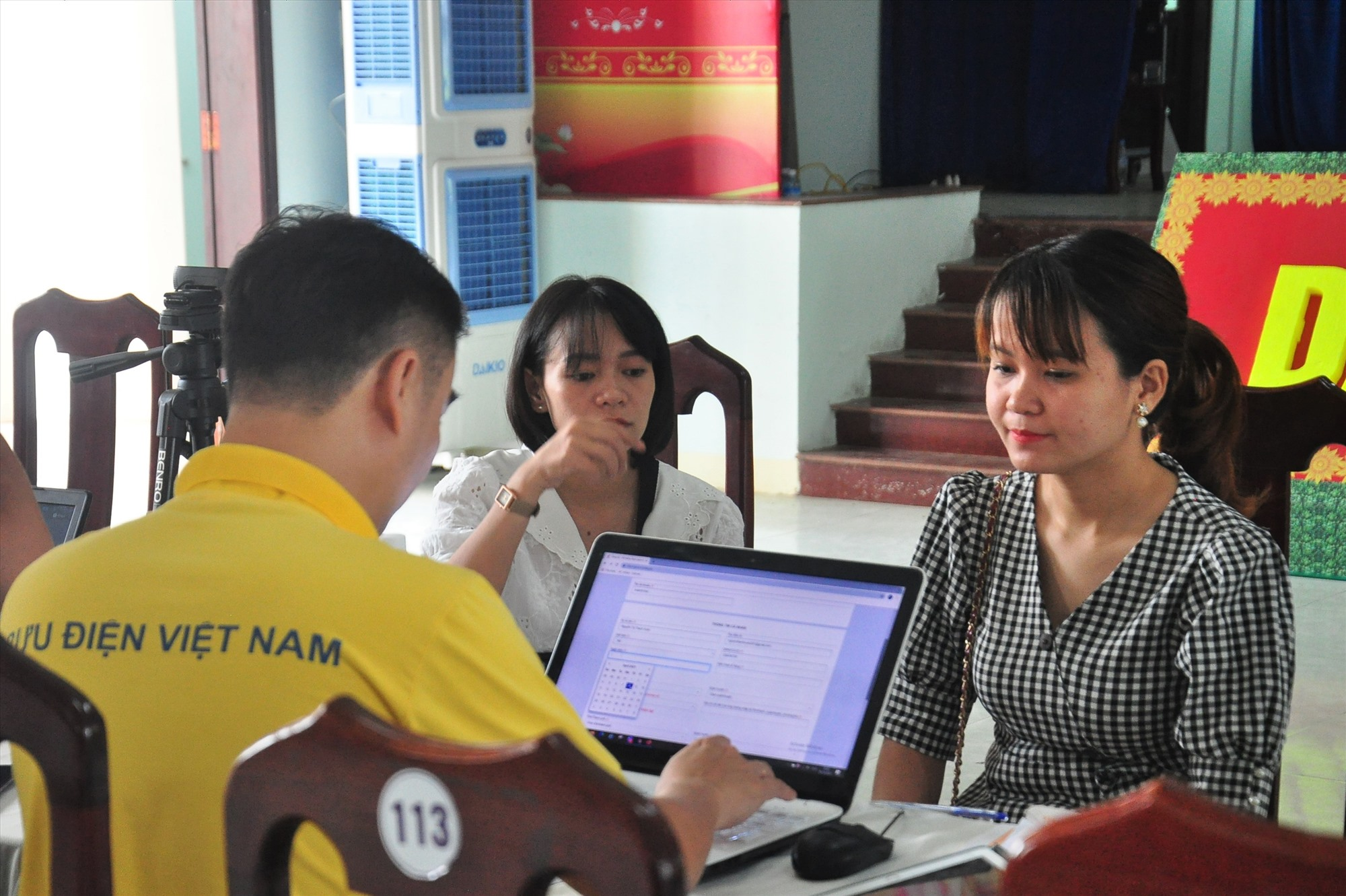 Cán bộ, người dân thị trấn Nam Phước được nhân viên bưu điện thực hiện định danh xác thực điện tử miễn phí. Ảnh: VINH ANH