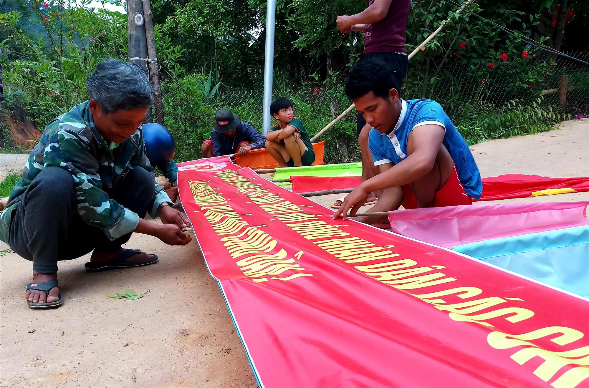 Đồng bào vùng cao Nam Giang cùng phụ giúp trang trí cổng chào ngày hội bầu cử sớm.Ảnh: ALĂNG NGƯỚC