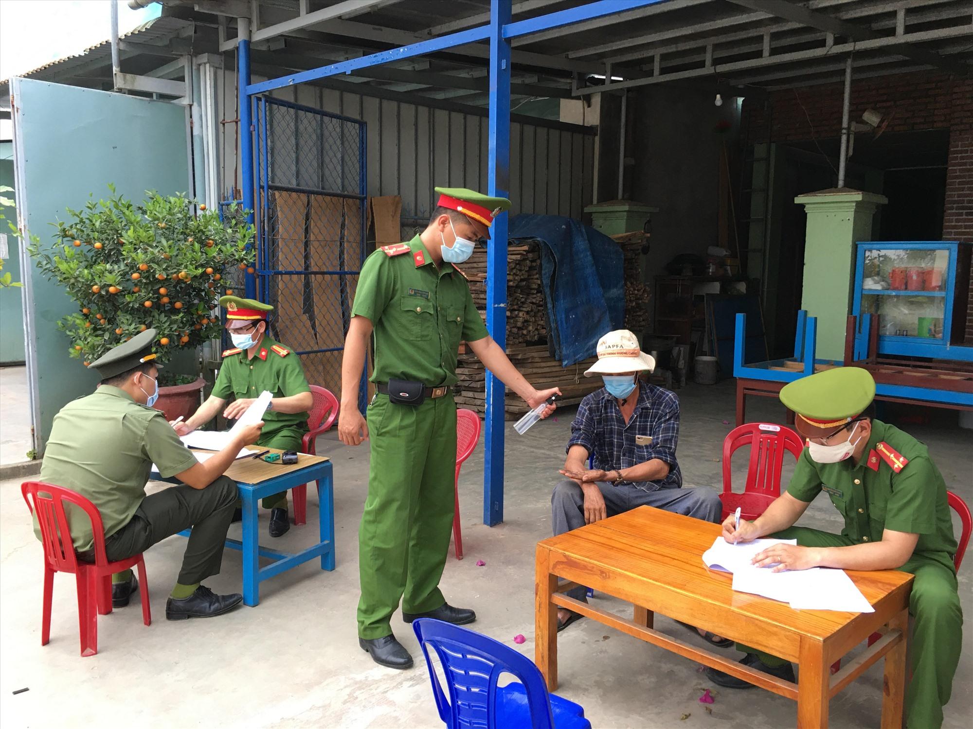 Công an huyện Phú Ninh lập biên bản xử phạt người vi phạm quy định đeo khẩu trang. Ảnh: H.C