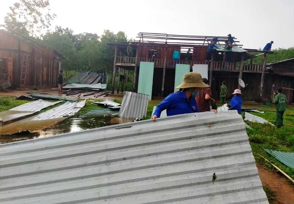 Một nữ đoàn viên góp sức vận chuyển tôn đến vị trí nhà đang sửa chữa. Ảnh: Đ.N