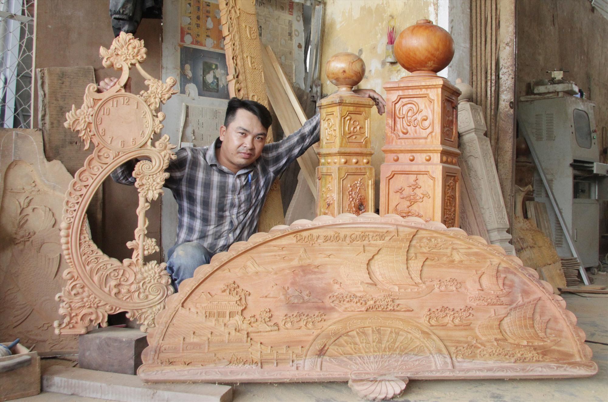 Anh Hồ Văn Công bên những sản phẩm gia công gỗ mỹ nghệ của mình chế tác. Ảnh: H.Q