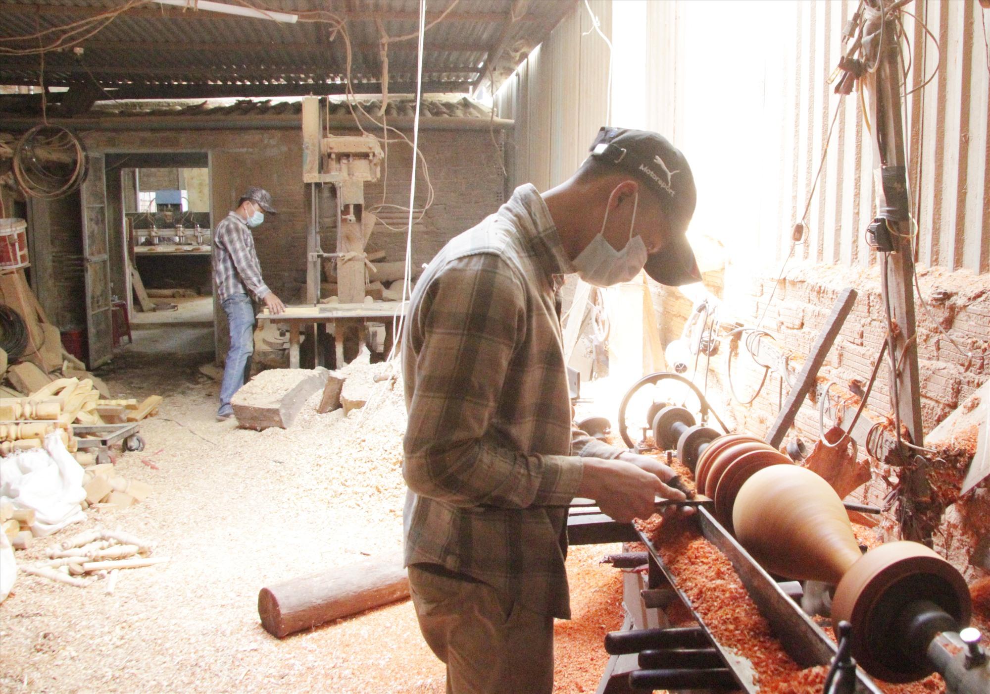Người thợ tại Tiện gỗ CNC Thành Công đang chế tác hình thụ một chiếc lục bình gỗ bằng máy móc hiện đại. Ảnh: H.Q