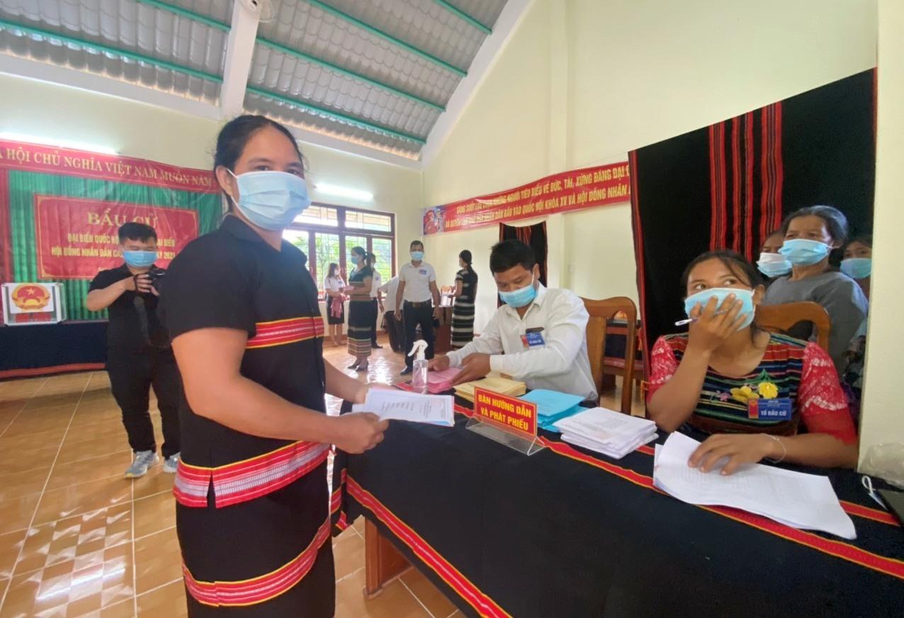 Cử tri thôn 58 làm thủ tục và được tổ bầu cử hướng dẫn trước khi bỏ phiếu.