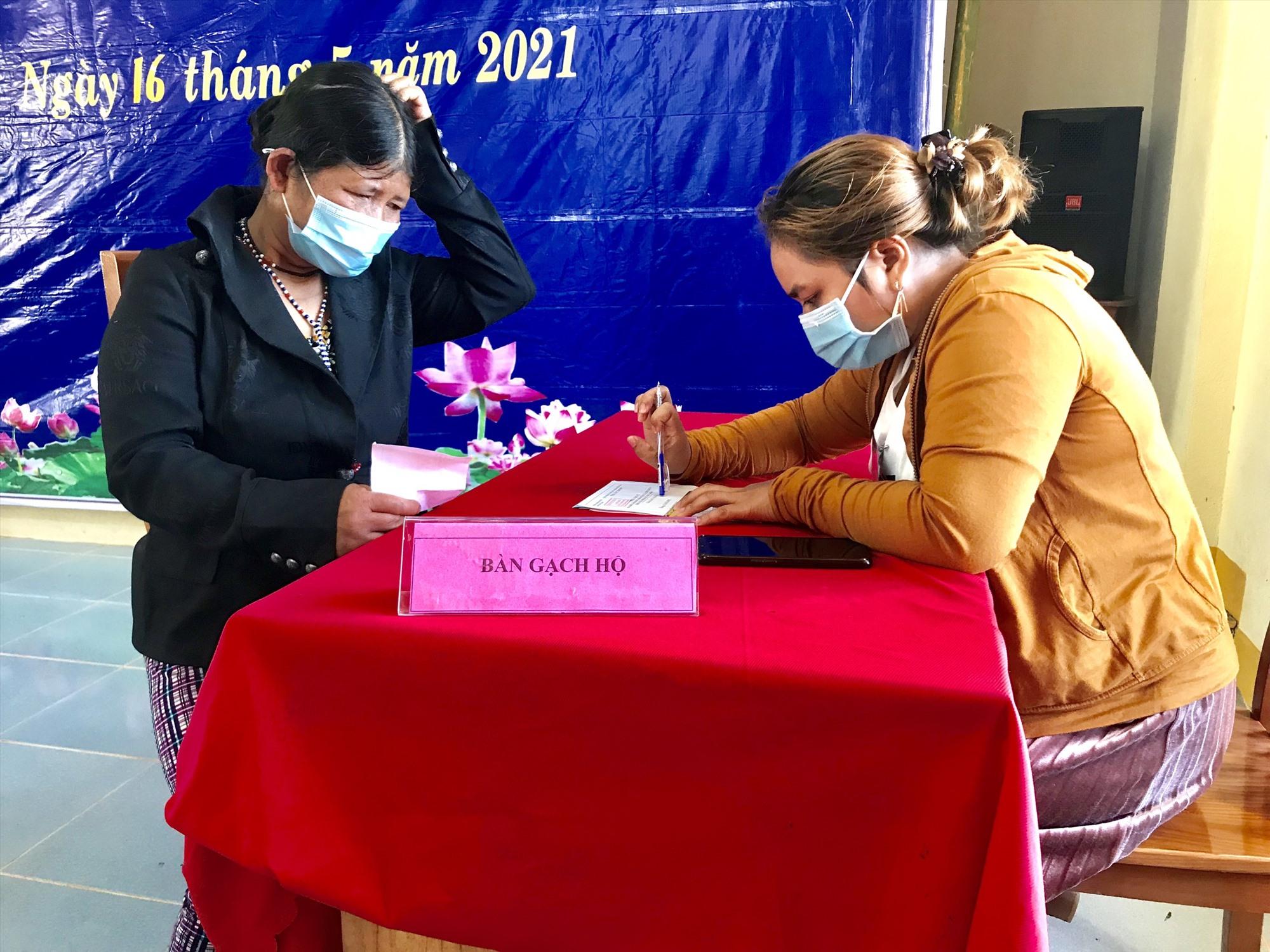 Cử tri xã Chơ Chun nhờ người viết hộ phiếu bầu.