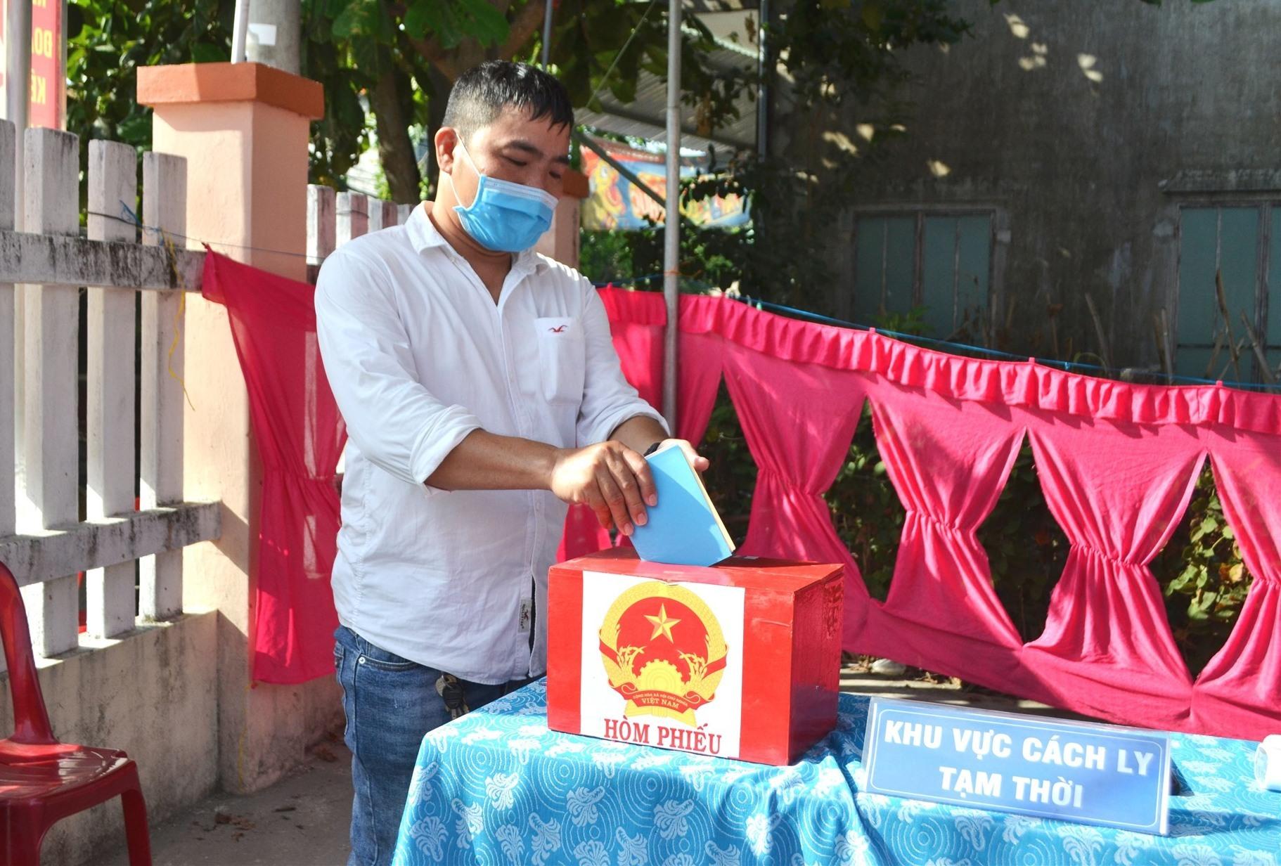 Cử tri bị sốt thực hiện quyền bầu cử trước khi được đưa đến Trạm Y tế phường Vĩnh Điện. Ảnh: TÚ-ĐOAN