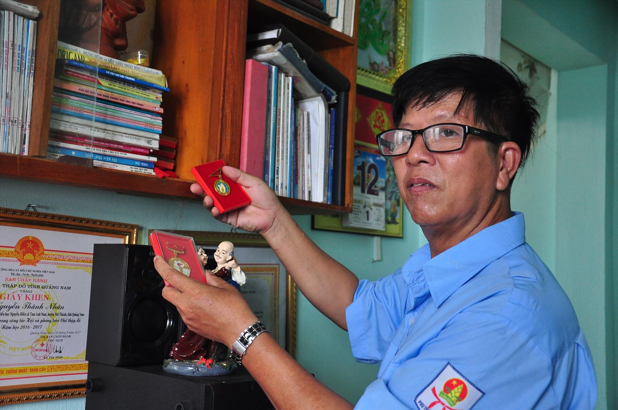 Thầy Nguyễn Thành Nhân lữu giữ cẩn thận những kỷ vật và các huy hiệu được khen tặng trong thời gian công tác của mình. Ảnh: VINH ANH