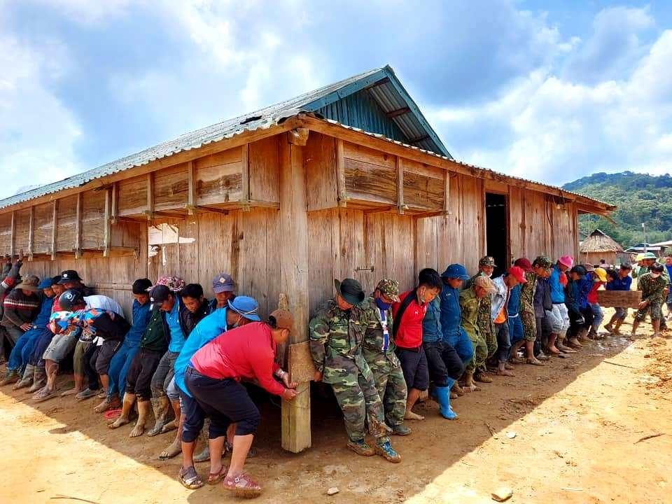 Chiến sĩ Đồn Biên phòng Ga Ry (Tây Giang) góp sức di chuyển căn nhà người dân địa phương khỏi điểm sạt lở. Ảnh: ALĂNG NGƯỚC