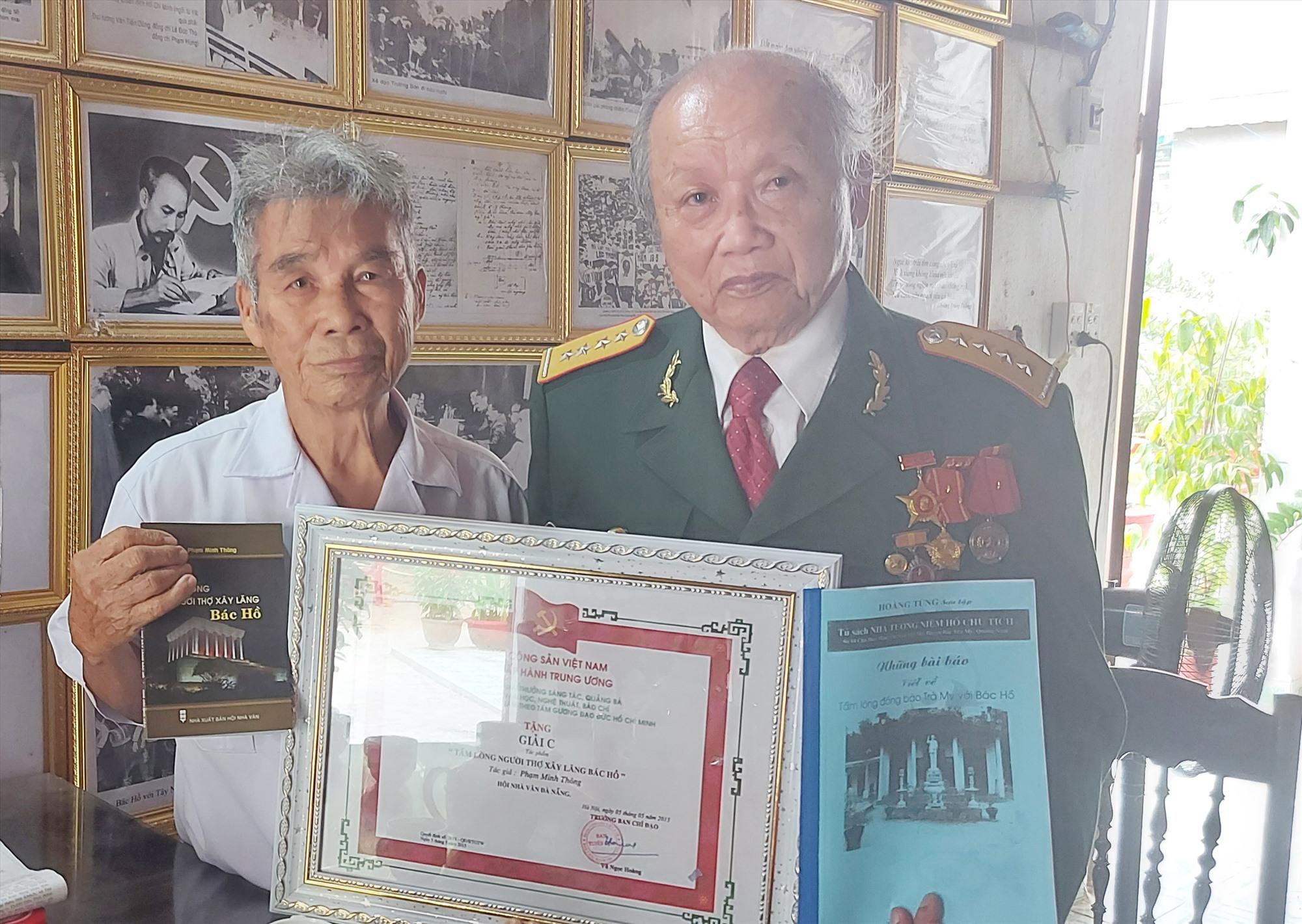 Cụ Phạm Minh Thông (bên phải) và cụ Võ Như Thông tặng sách quý viết về việc xây vườn hoa trong Lăng Bác Hồ và Nhà thờ Bác Hồ. Ảnh: LÊ ANH DŨNG