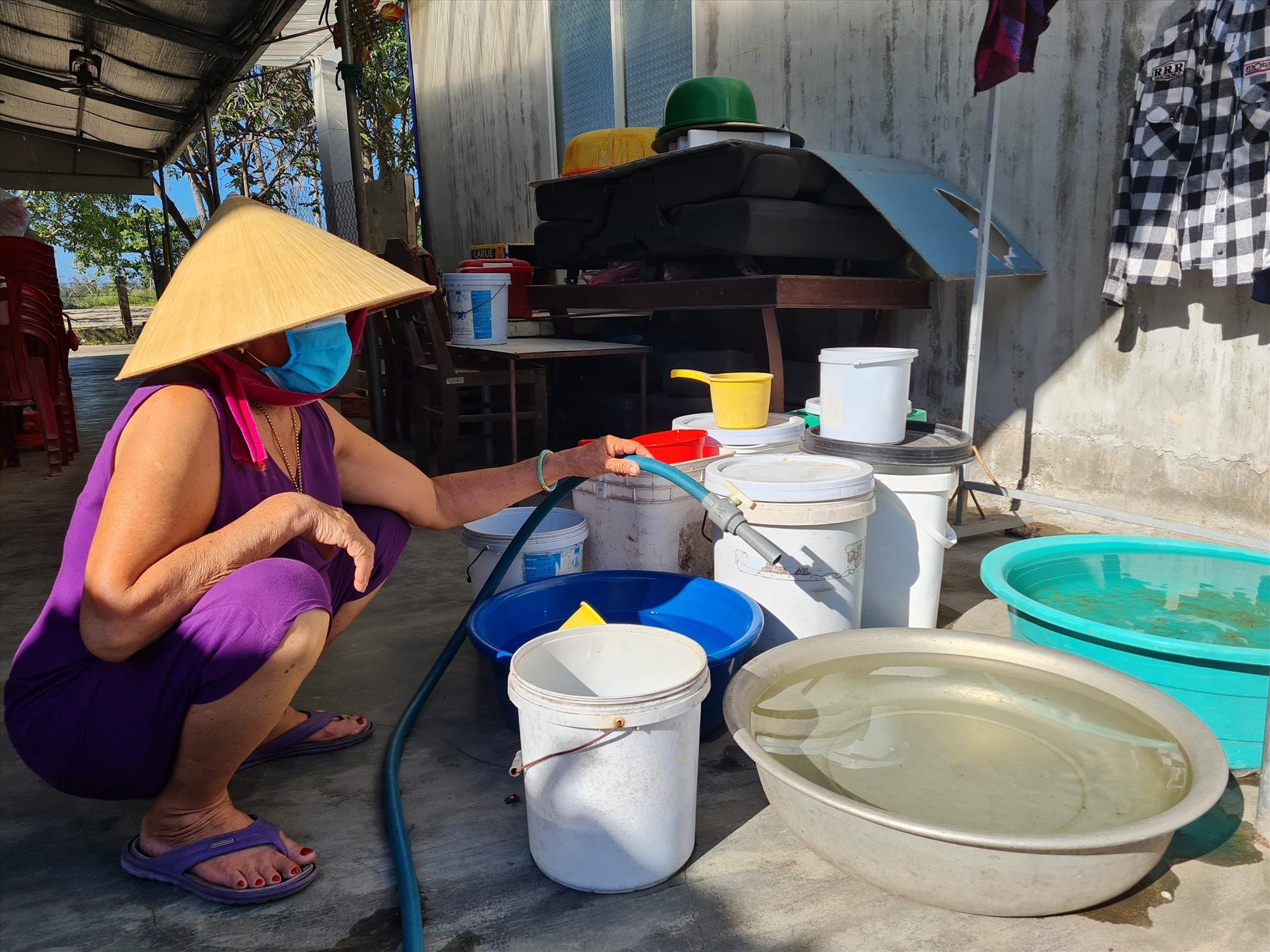 Nhiều hộ dân ở tổ 1, thôn Hòa Bình, xã Tam Hòa phải túc trực để bơm nước chứa vào các xô, thau để dành sử dụng song nguồn nước lúc có lúc không do ở xa nguồn. Ảnh: H.L