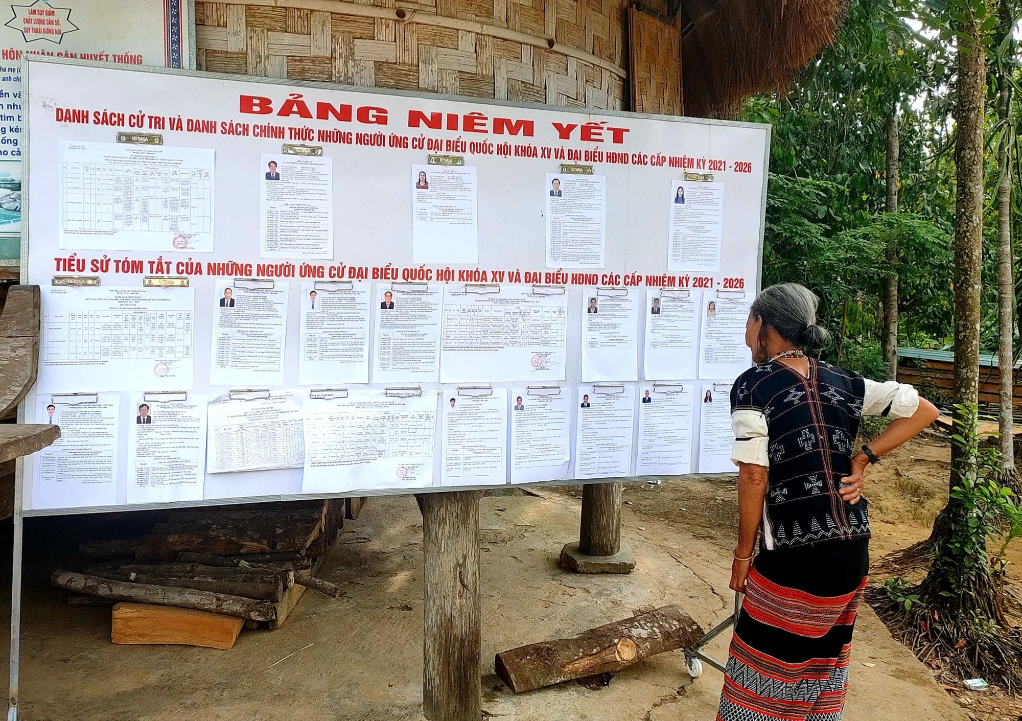 Một cụ bà Cơ Tu chăm chú chú tìm hiểu thông tin các cử tri trước ngày diễn ra bầu cử. Ảnh: THÁI NGUYỄN