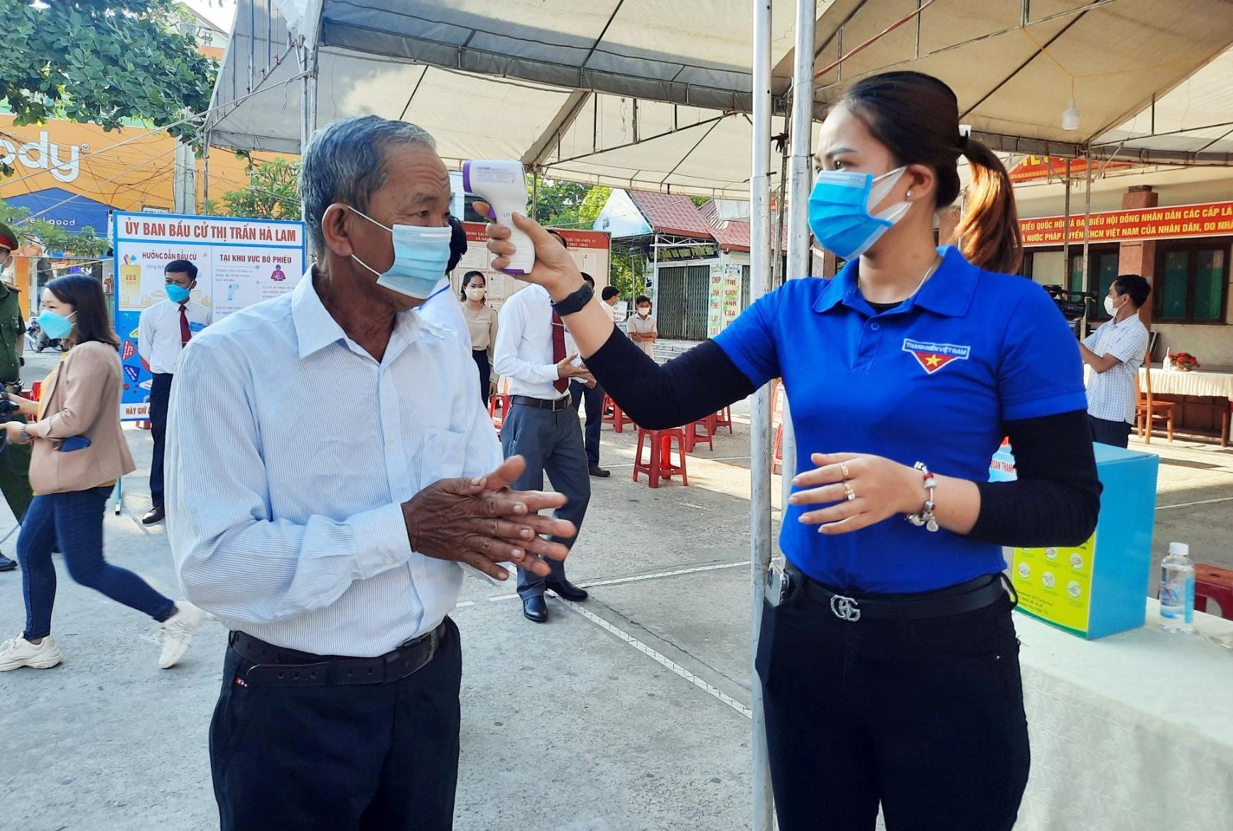 Cử tri được đo thân nhiệt trước khi vào khu vực bỏ phiếu tại khối phố 4, thị trấn Hà Lam.