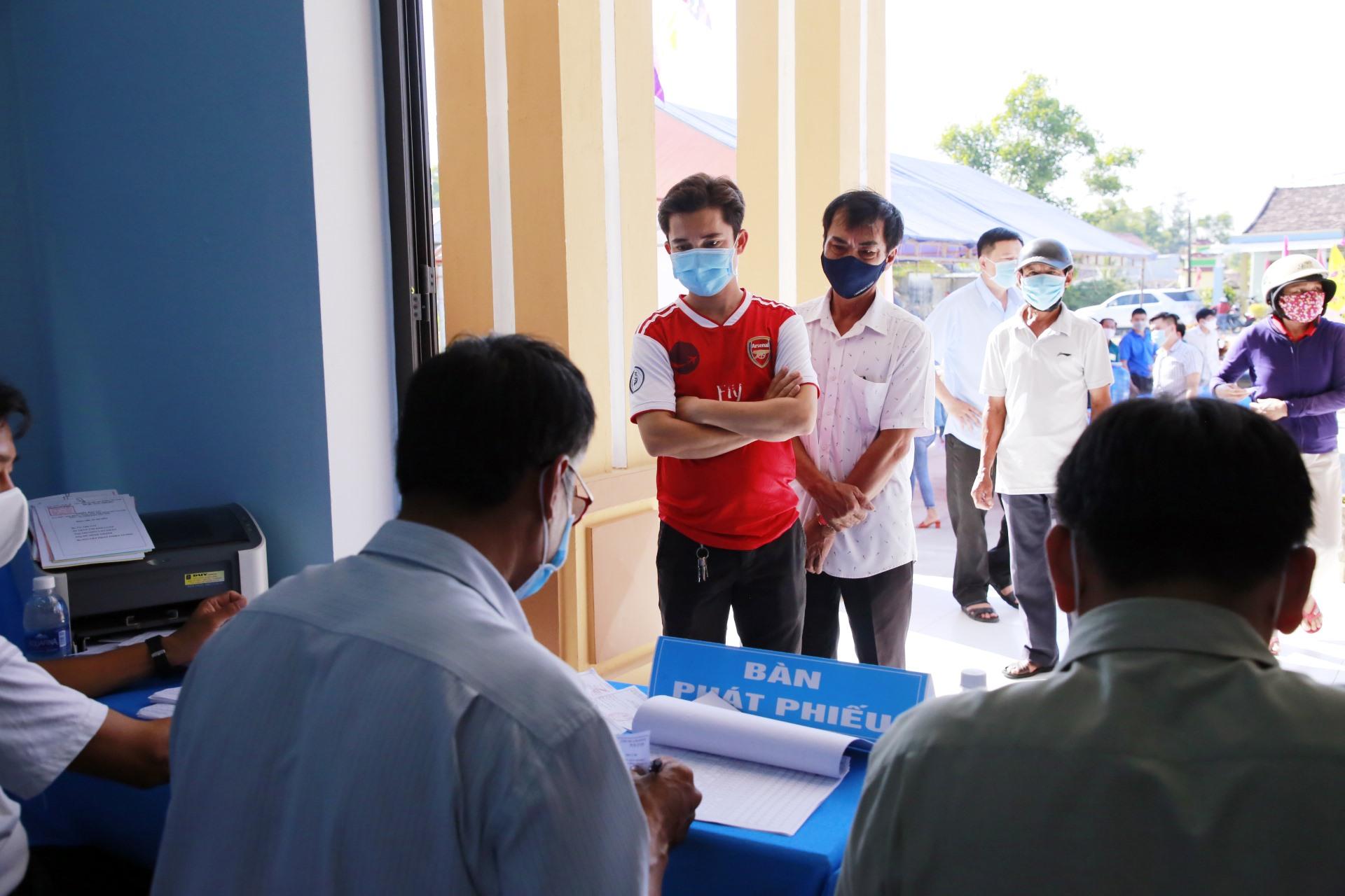 Xếp hàng giữ khoảng cách khi vào nhận phiếu bầu cử.