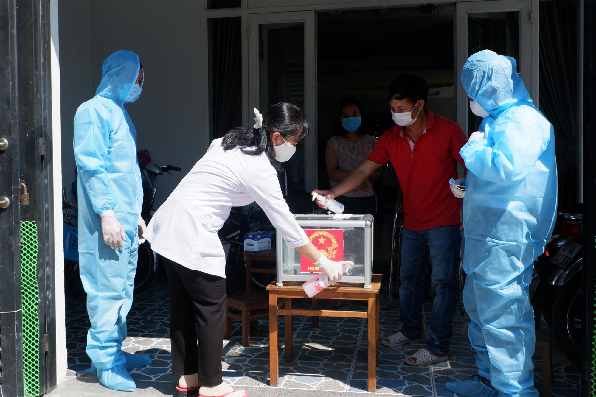 Nhân viên y tế khử khuẩn thùng phiếu phụ khi đưa đến nhà cử tri đang thực hiện cách ly.