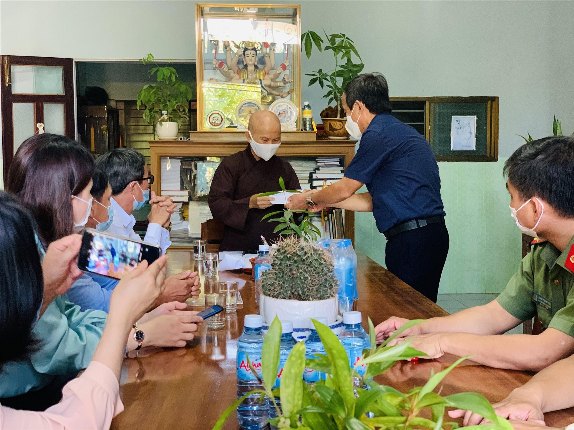 Lãnh đạo UBND huyện Duy Xuyên tặng quà cho đại diện chùa Ân Triêm (thị trấn Nam Phước). Ảnh: T.P