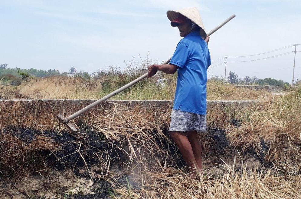 Một người dân đang tranh thủ đốt rạ, vệ sinh đồng ruộng đợi nước về mới tiến hành gieo sạ. Ảnh: Q.H