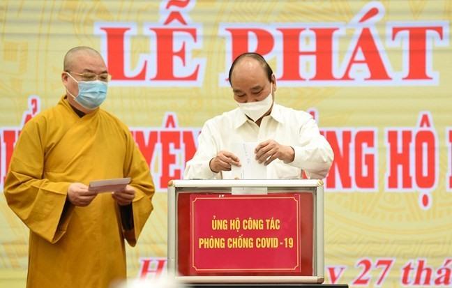 Chủ tịch nước Nguyễn Xuân Phúc và Chủ tịch UBTƯ MTTQ Việt Nam Đỗ Văn Chiến cùng các đại biểu chung tay ủng hộ công tác phòng, chống dịch