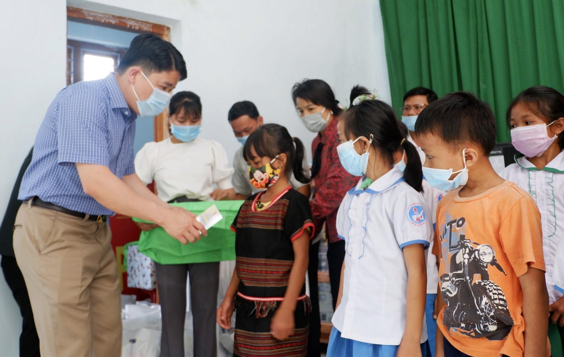 Phó Chủ tịch UBND tỉnh Trần Văn Tân tặng quà cho các em xã Trà Bui. Ảnh: X.H