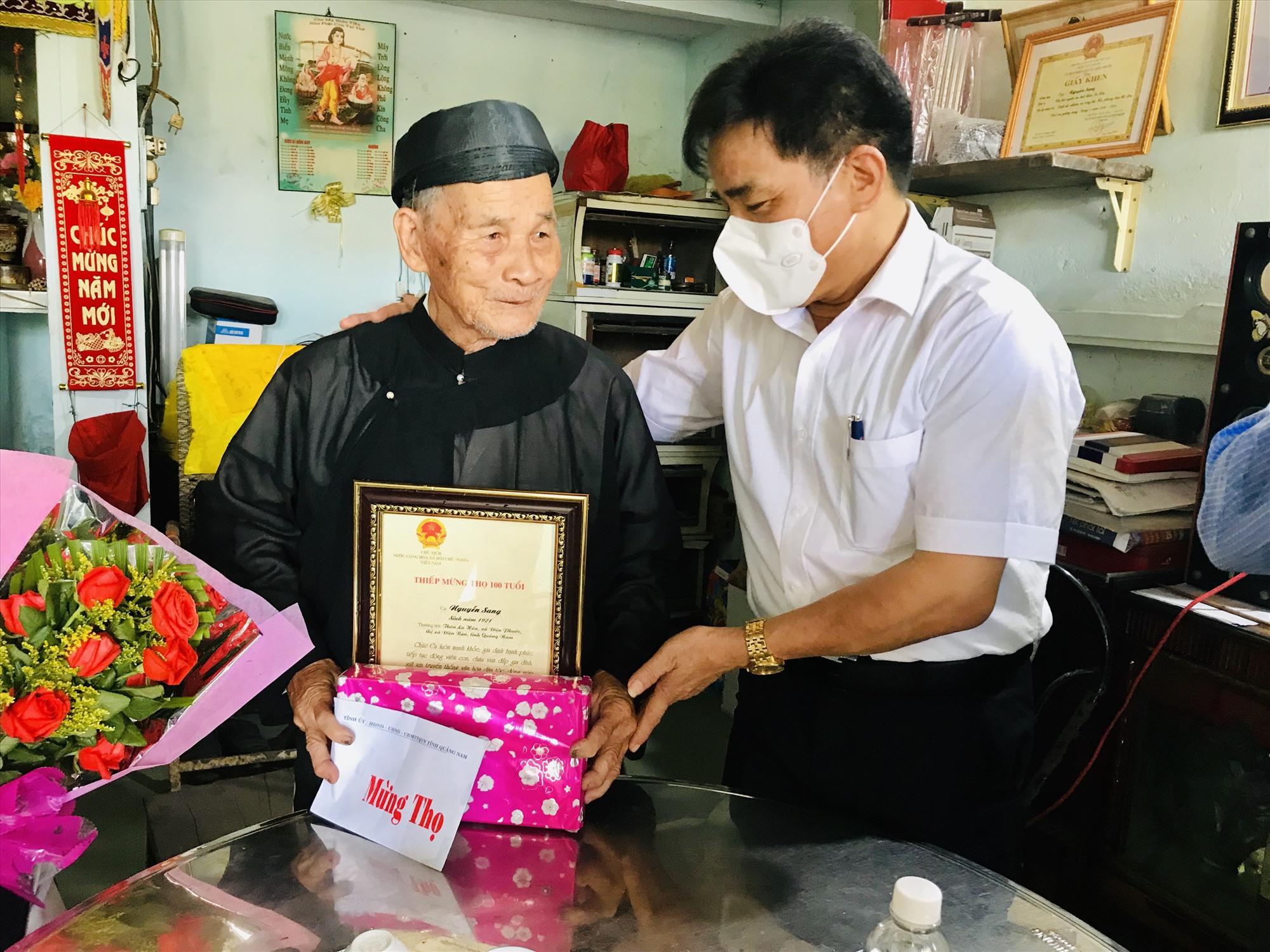 Phó Bí thư Thường trực Tỉnh ủy Lê Văn Dũng trao thiếp mừng thọ 100 tuổi của Chủ tịch nước cho cụ Nguyễn Sang. Ảnh: Q.T