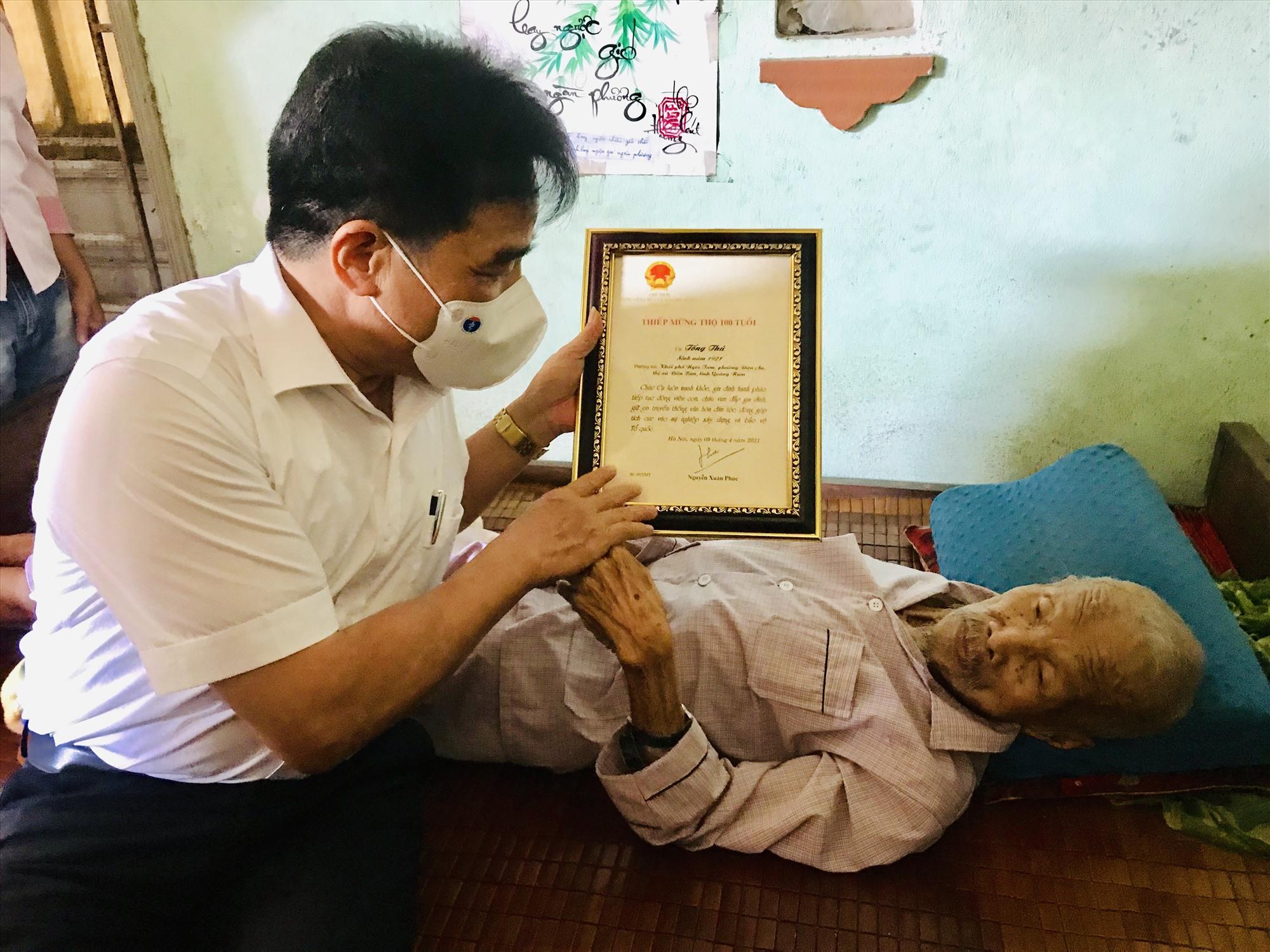 Trao thiếp mừng thọ 100 tuổi của Chủ tịch nước cho cụ Tống Thú. Ảnh: Q.T