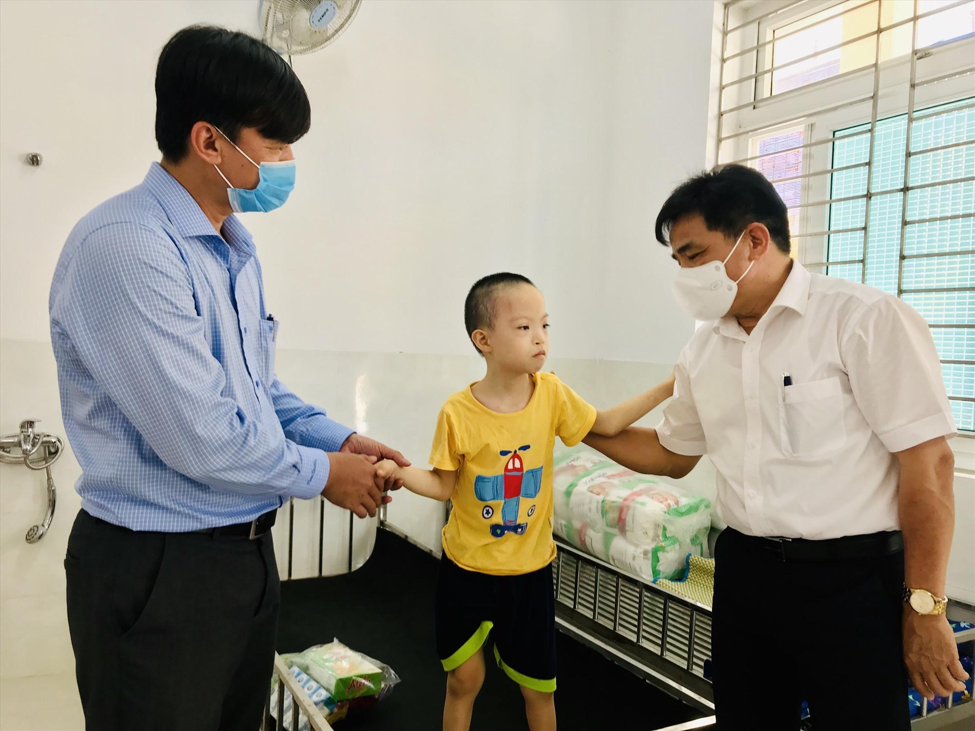 Đồng chí Lê Văn Dũng động viên một trẻ khuyết tật tại trung tâm. Ảnh: Q.T