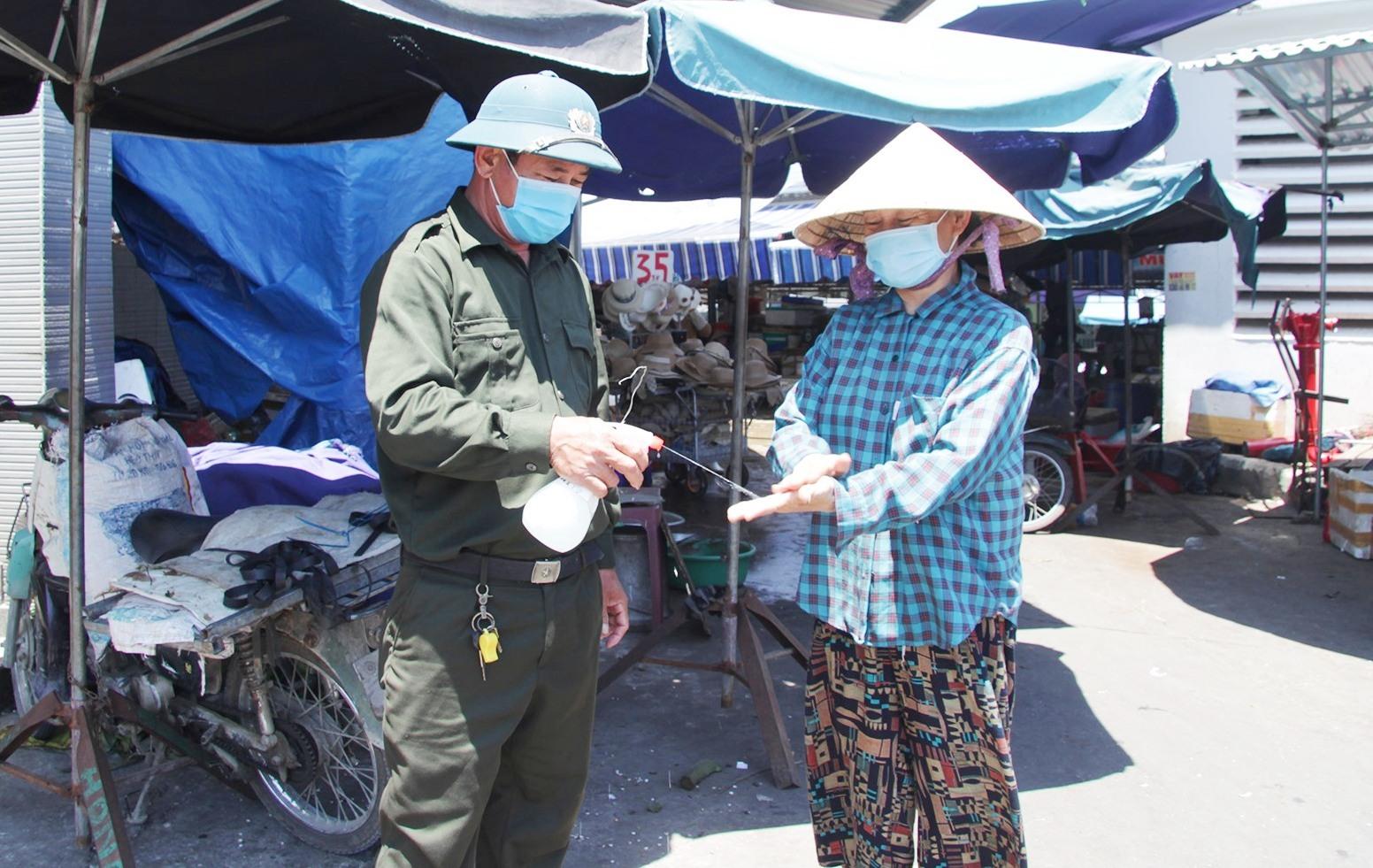 Ban quản lý chợ xịt sát khuẩn tay cho người dân khi vào mua bán. Ảnh: H.Q