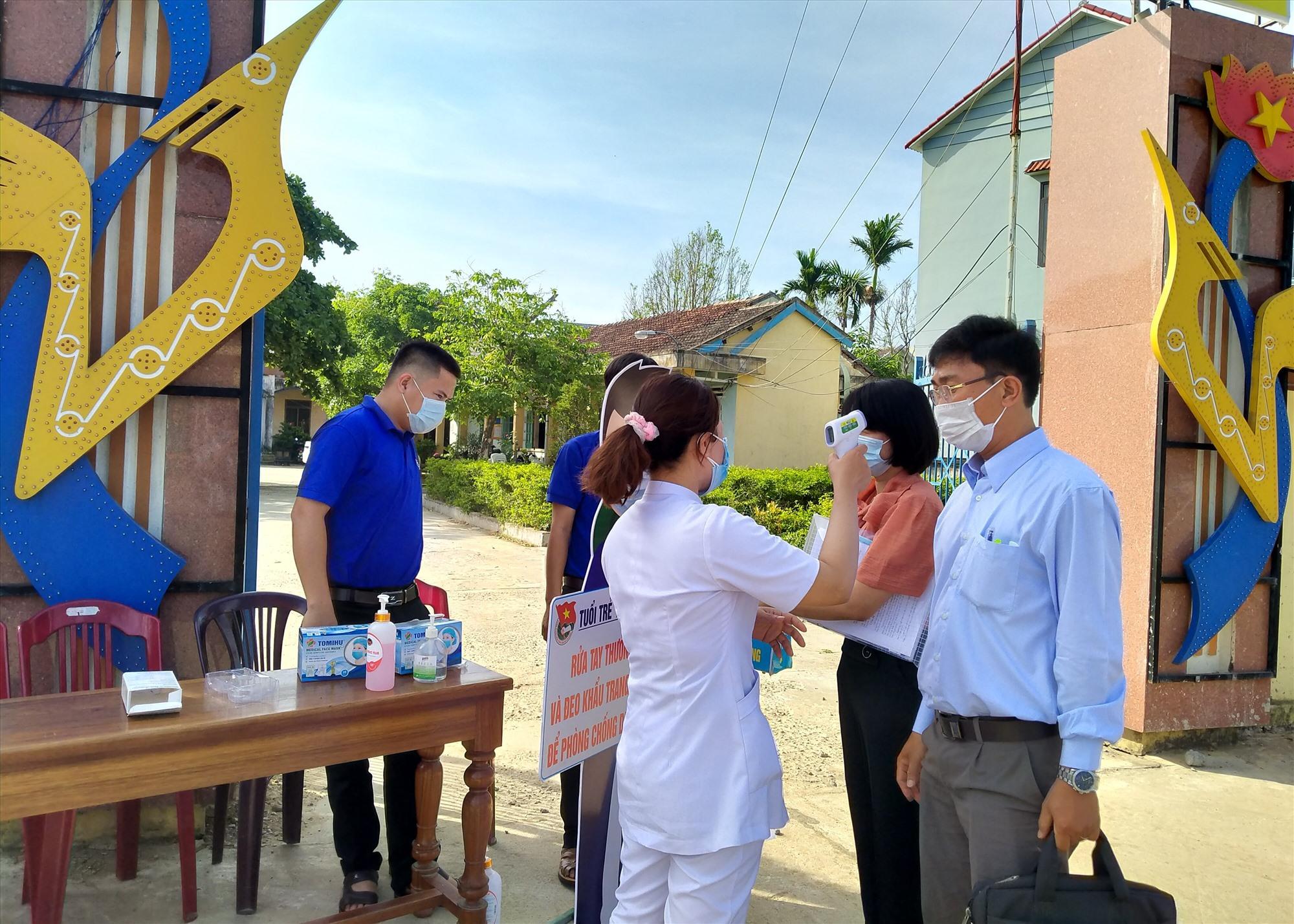 Kiểm tra đo thân nhiệt và rửa tay sát khẩu trước khi vào hội trường tiếp xúc cử tri với người ứng cử đại biểu HĐND tỉnh khóa X. Ảnh: N.Đ