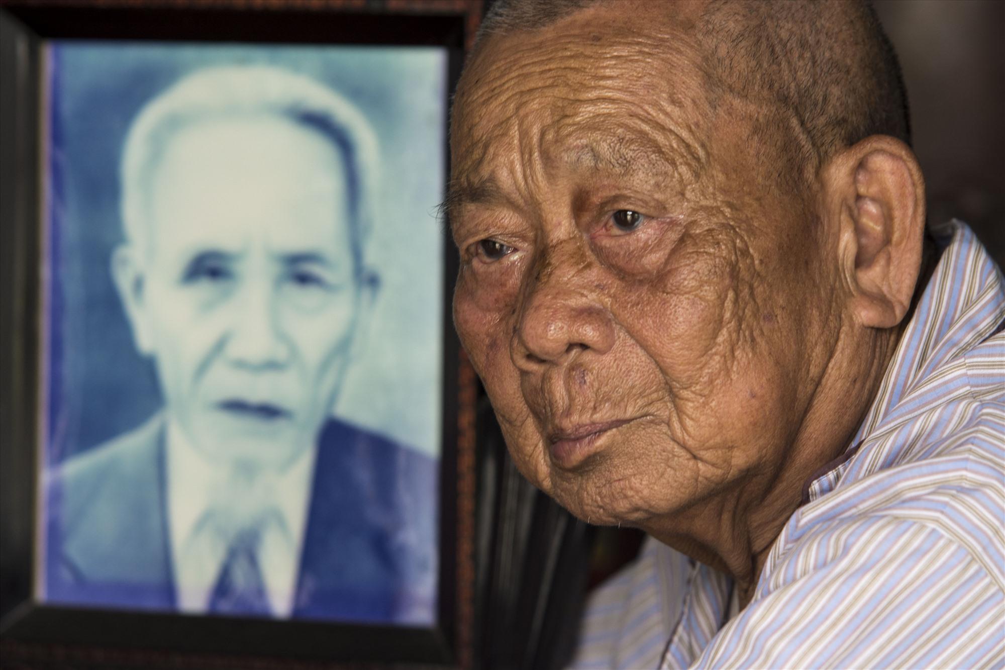 Ông Lương Văn Chi với di ảnh cha Lương Văn Ngao, người từng cầm lái ghe bầu. Ảnh: Văn Chương
