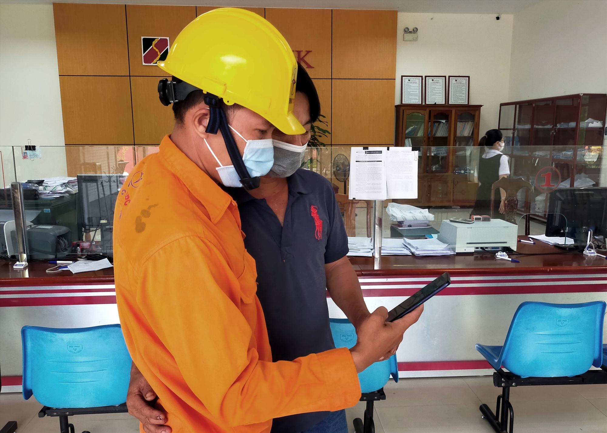 Nhân viên Điện lực Hiệp Đức đến tận ngân hàng hỗ trợ khách cài đặt ứng dụng công nghệ số trong thanh toán tiền điện. Ảnh: K.P
