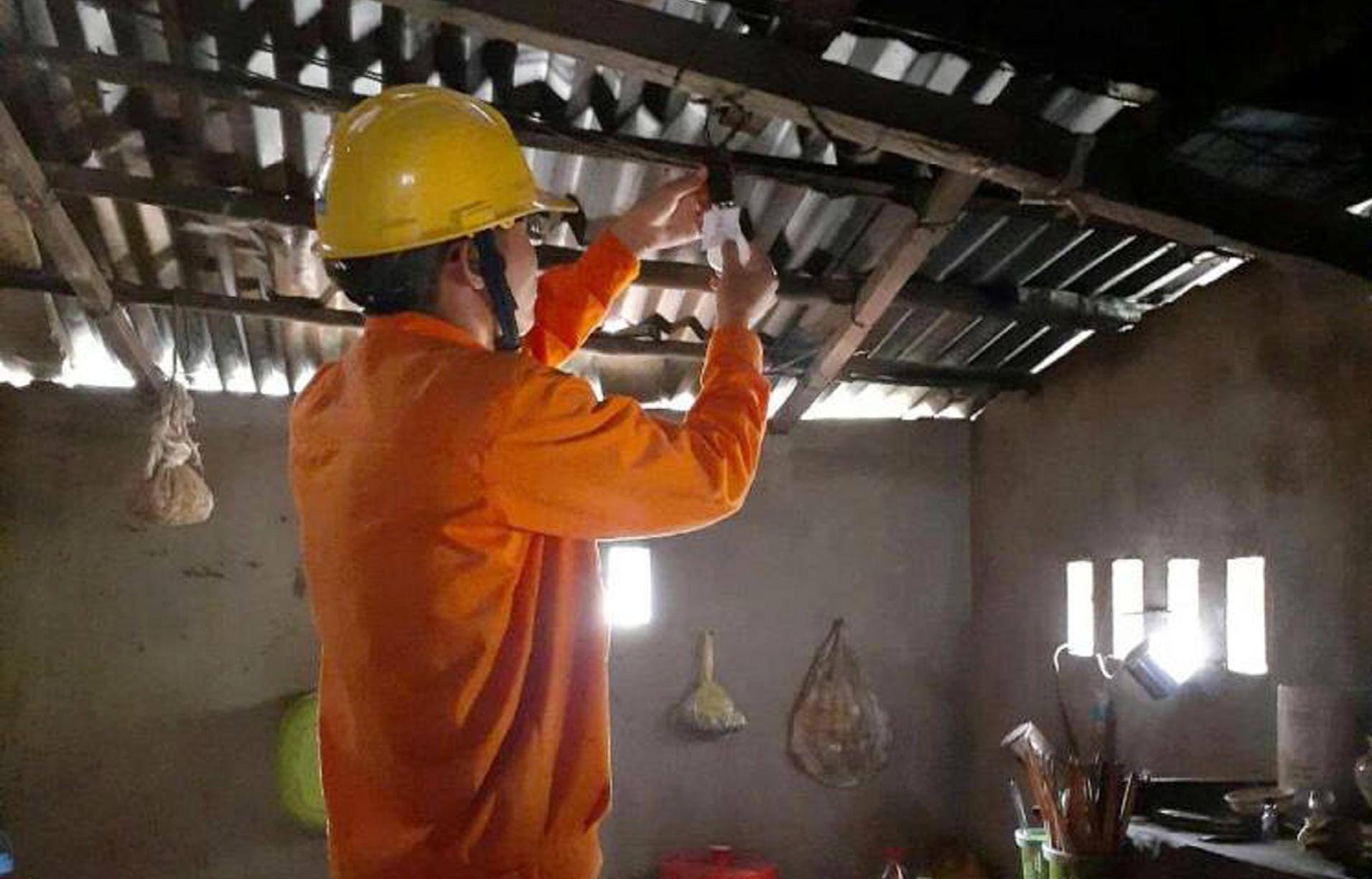 Nhân viên điện lực hỗ trợ người dân thay bóng đèn chiếu sáng tiết kiệm điện năng. Ảnh: T.D