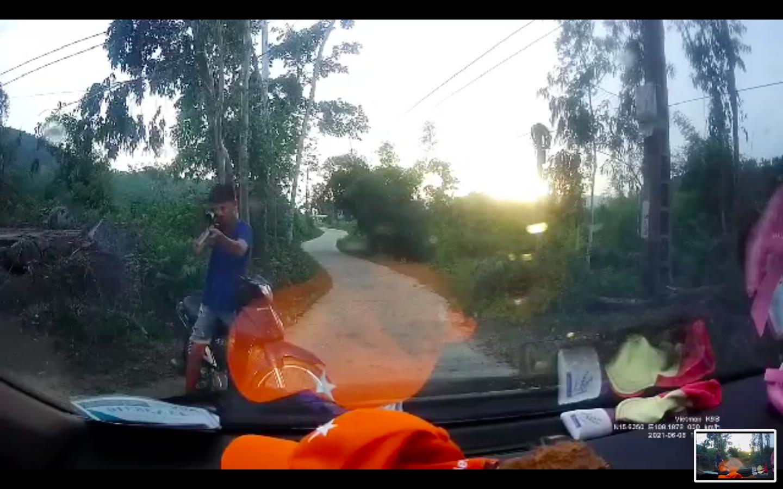 """Người đi xe máy liên tục cầm """"súng tự chế"""" chĩa về phía người đi ô tô. Ảnh cắt từ video clip"""