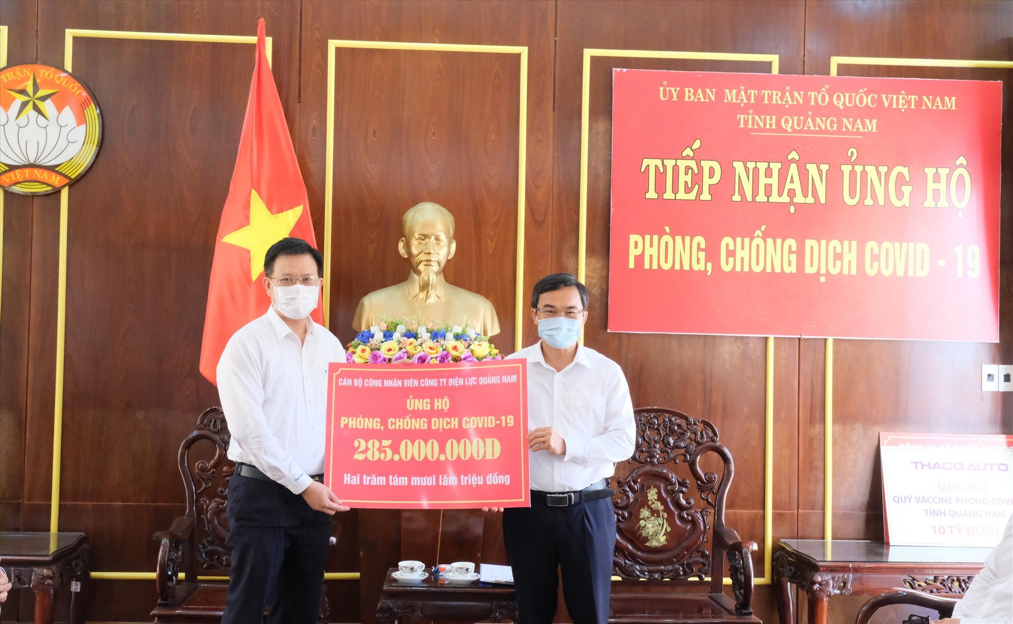 Ông Nguyễn Hữu Khánh - Giám đốc PC Quảng Nam (bên trái) trao số tiền ủng hộ Quỹ vắc xin phòng Covid-19 cho Ủy ban MTTQVN tỉnh