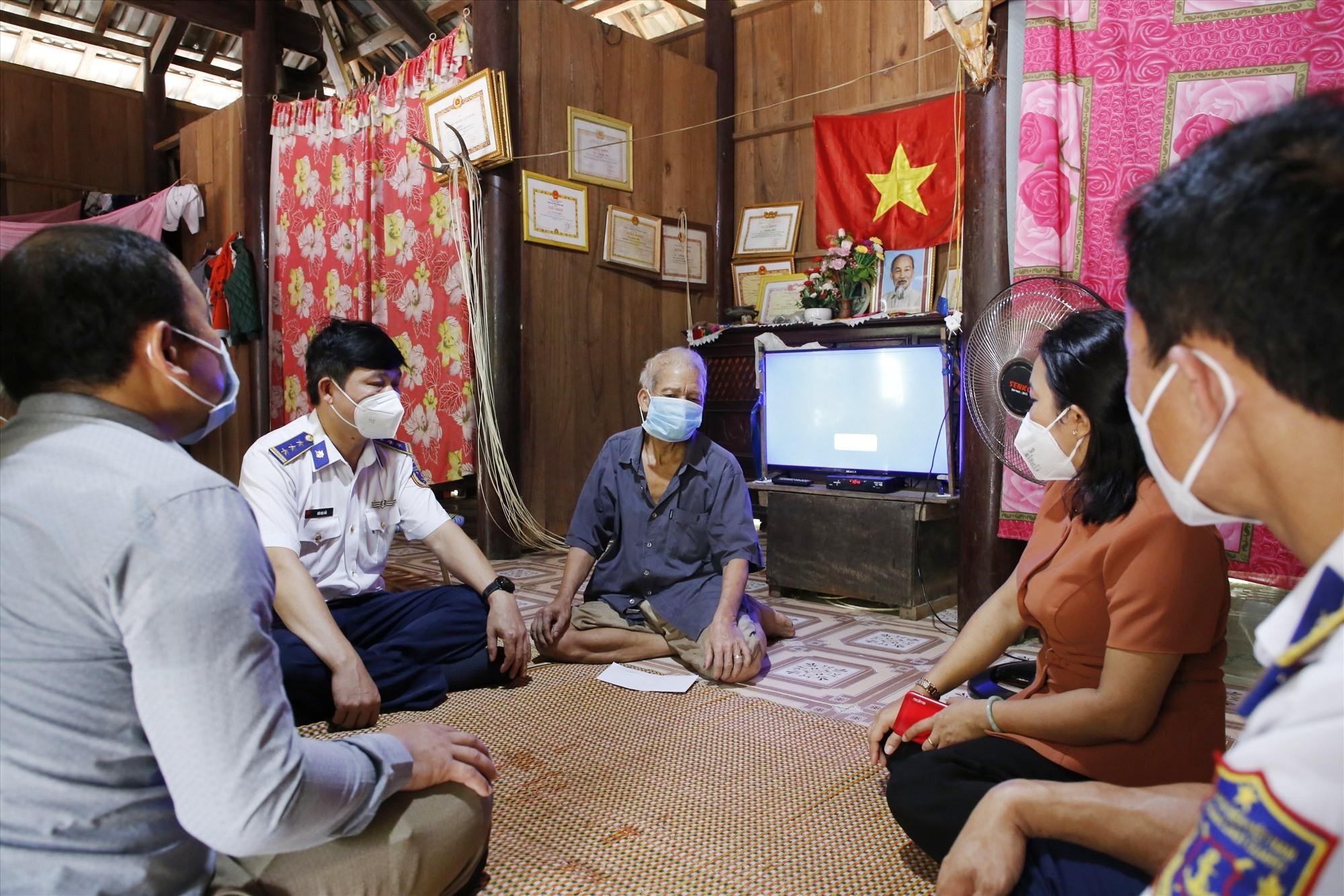 Thượng tá Bùi Đại Hải và Trưởng Ban Dân vận Tỉnh ủy Huỳnh Thị Thùy Dung đến thăm hỏi, tặng quà cho ông Alăng Biêu, người có uy tín tại thôn Bến Hiên (xã Kà Dăng). Ảnh: T.C
