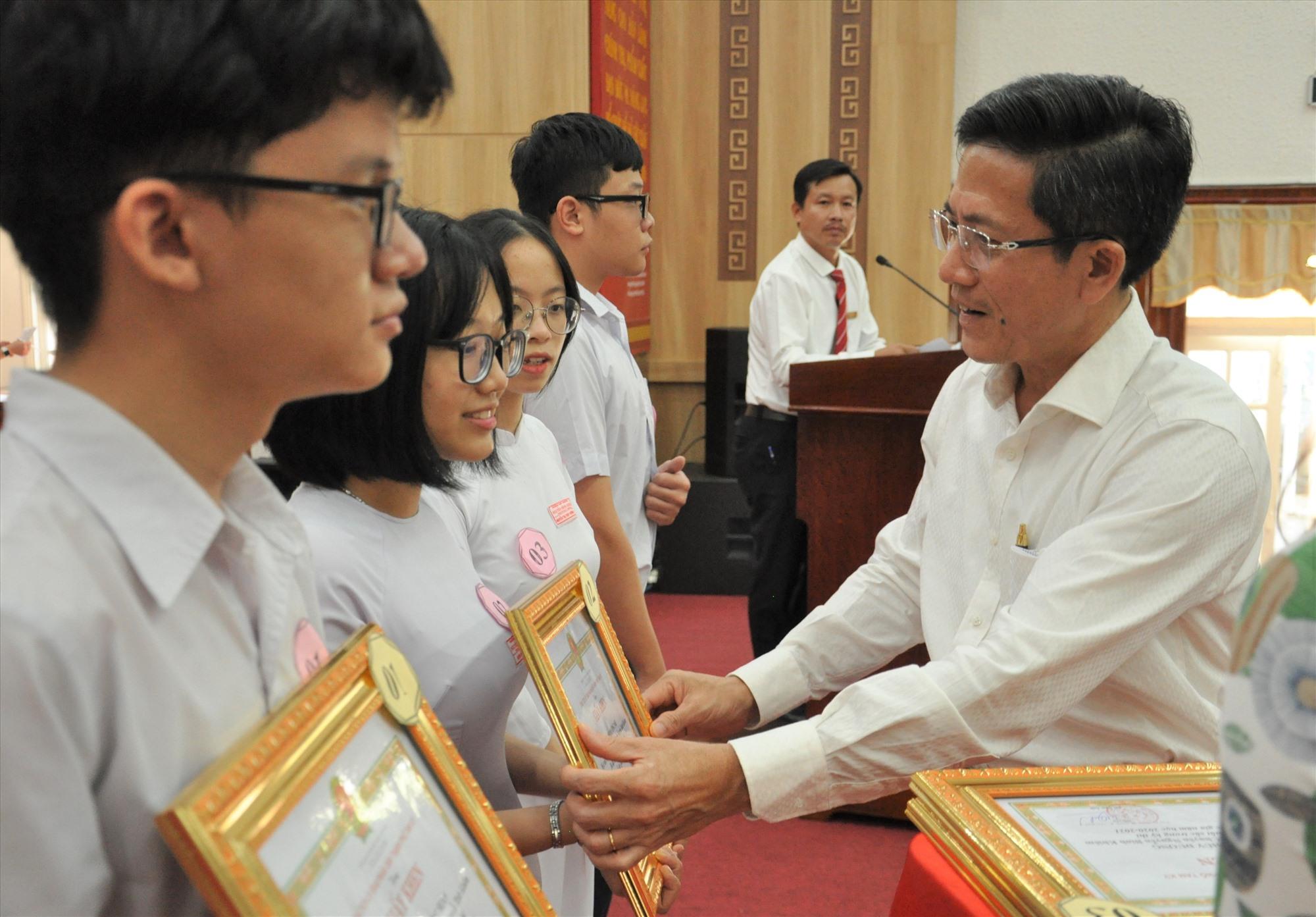 Bí thư Thành ủy Tam Kỳ Trần Nam Hưng tặng giấy khen và tiền thưởng cho HS xuất sắc. Ảnh: X.P