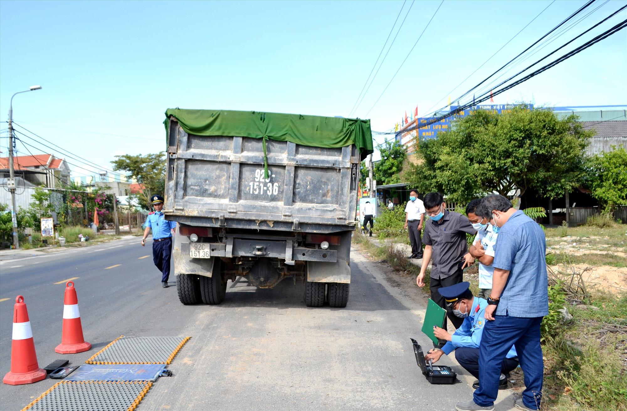 Thanh tra Sở GTVT sử dụng cân xách tay để kiểm tra tải trọng xe trên quốc lộ 40B. Ảnh: T.C.T