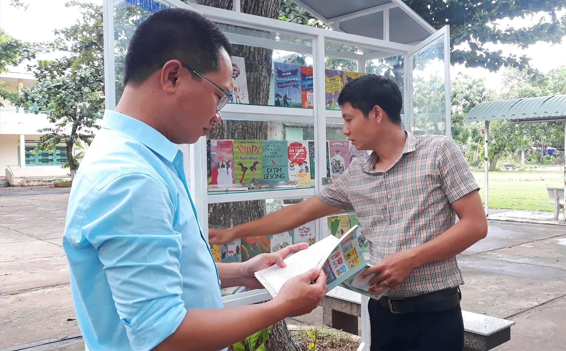 """Thầy Tăng Văn Chung (trái) và thầy Nguyễn Khắc Việt đọc sách ở """"cây sách"""" sân trường. Ảnh: C.N"""