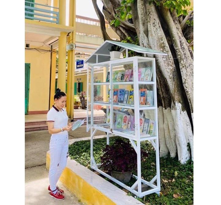 """Giáo viên Trường THPT Nguyễn Duy Hiệu đọc sách ở """"cây sách"""" sân trường. Ảnh: H.T"""
