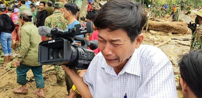 Phóng viên Đoàn Hữu Trung - TTXVN quay máy đi chỗ khác, bật khóc khi thi thể một em bé được đưa ra từ bùn đất ở Trà Leng, 2020. Ảnh: HOÀNG THẾ LỰC