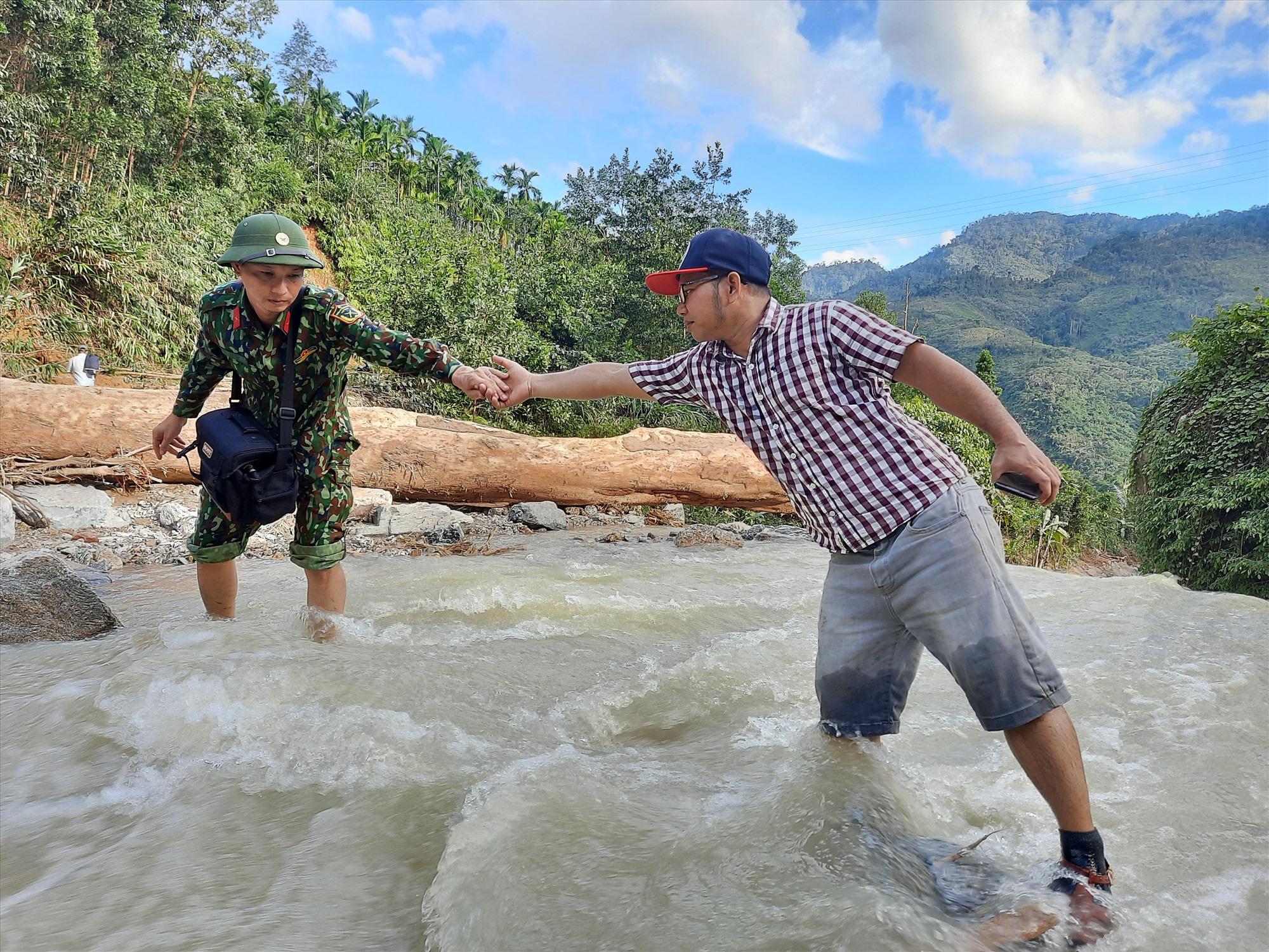 Nhà báo Alăng Ngước (bên phải) hỗ trợ đồng nghiệp kênh Truyền hình Quốc phòng Việt Nam vượt lũ trên chuyến tác nghiệp tại Trà Leng. Ảnh: Đ.N