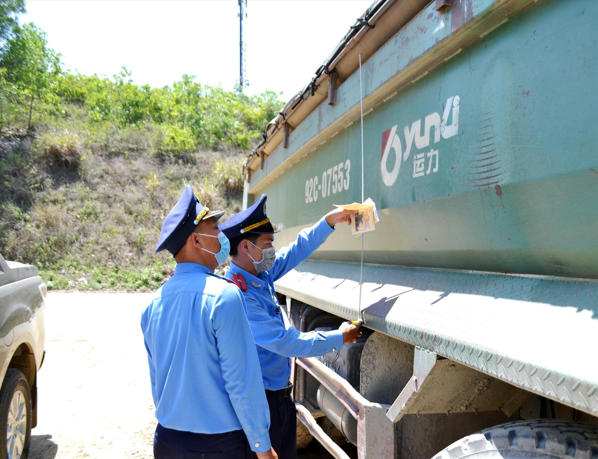 Thành viên Tổ kiểm tra liên ngành cấp tỉnh đo kích thước thùng xe tải chở hàng trên tuyến ĐT609 qua địa phận Đại Lộc. Ảnh: N.B