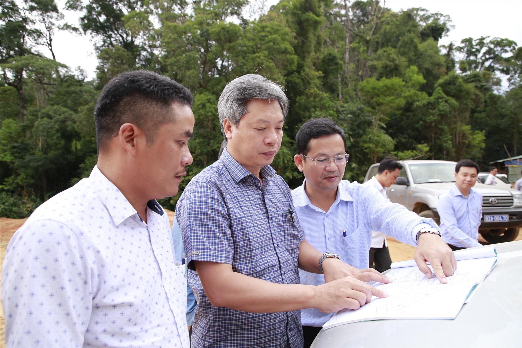 Phó Chủ tịch UBND tỉnh Hồ Quang Bửu trao đổi với lãnh đạo huyện Phước Sơn về tiến độ thực hiện mặt bằng khu tái định cư thôn 3 (thôn 6 cũ) của xã Phước Lộc.